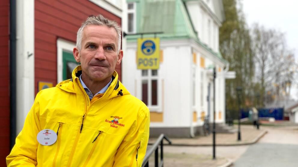 Joacim Johansson i gul jacka tittar ut över Astrid Lindgrens värld.