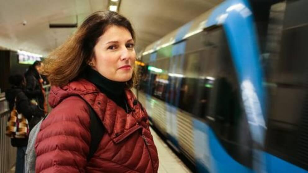 Kvinna framför åkande tunnelbanetåg
