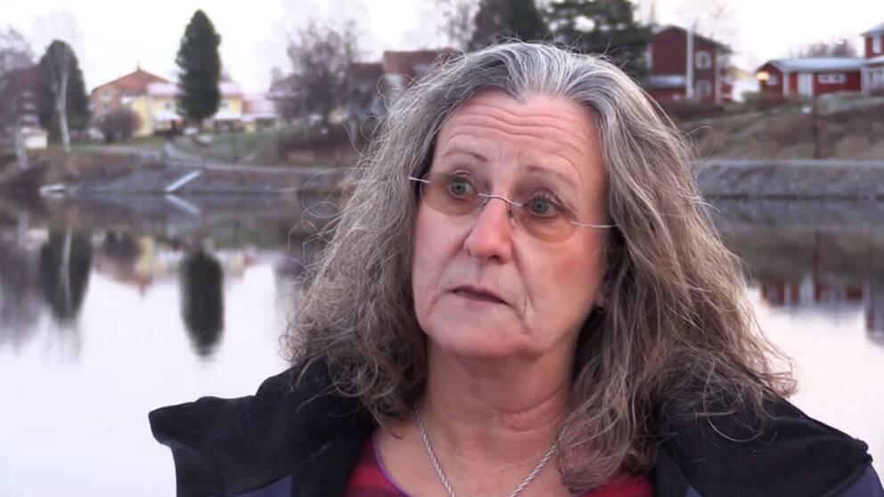En kvinna med tonade glasögon intervjuas vid ett vattendrag