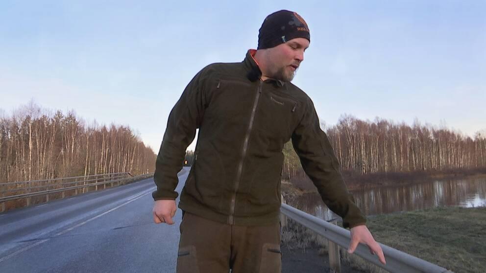 man i friluftskläder och mössa står på en vägbro över vattendrag och visar platsen, kala träd i bakgrunden