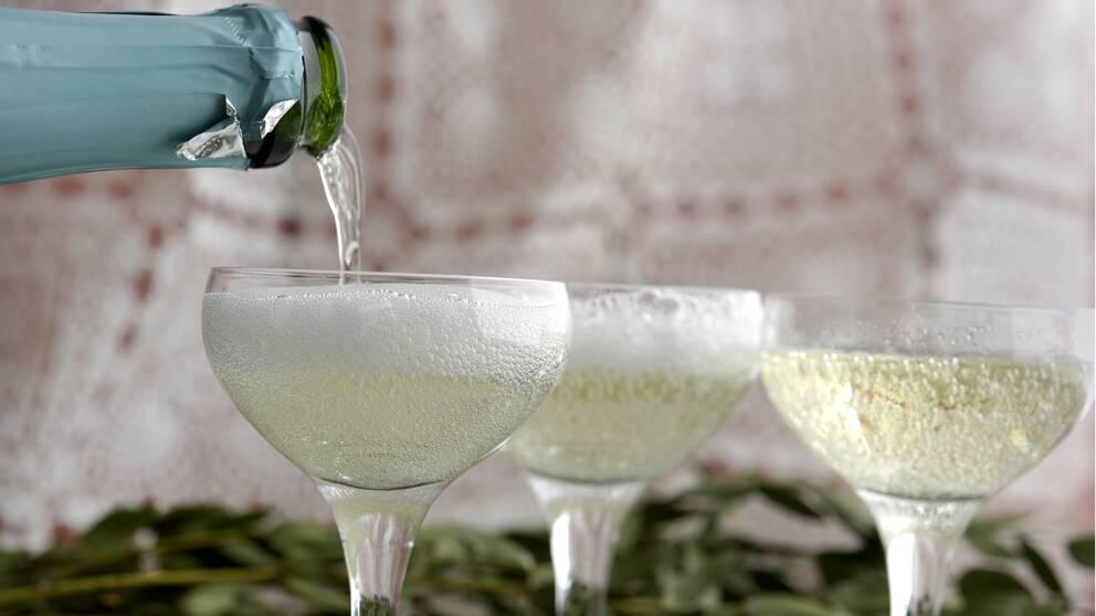Bilden föreställer tre stycken coupeglas med mousserande vin i. I det vänstra hörnet av bilden syns en grön flaskhals med turkos folie på. Någon häller mousserande vin från flaskan och ner i det vänsta coupeglaset.