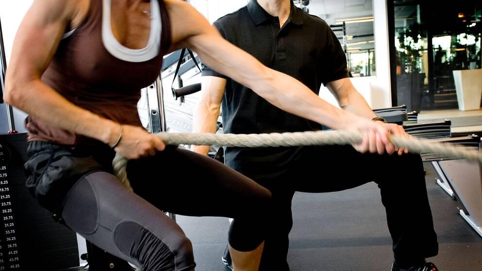 två personer i ett gym som gymar.