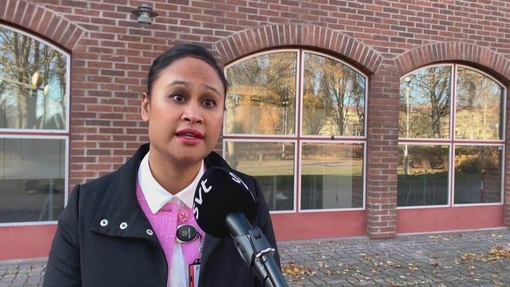 Johanna Munters Olsson intervjuas utomhus. Har på sig en vit skjorta, en rosa tröja och en svart jacka.