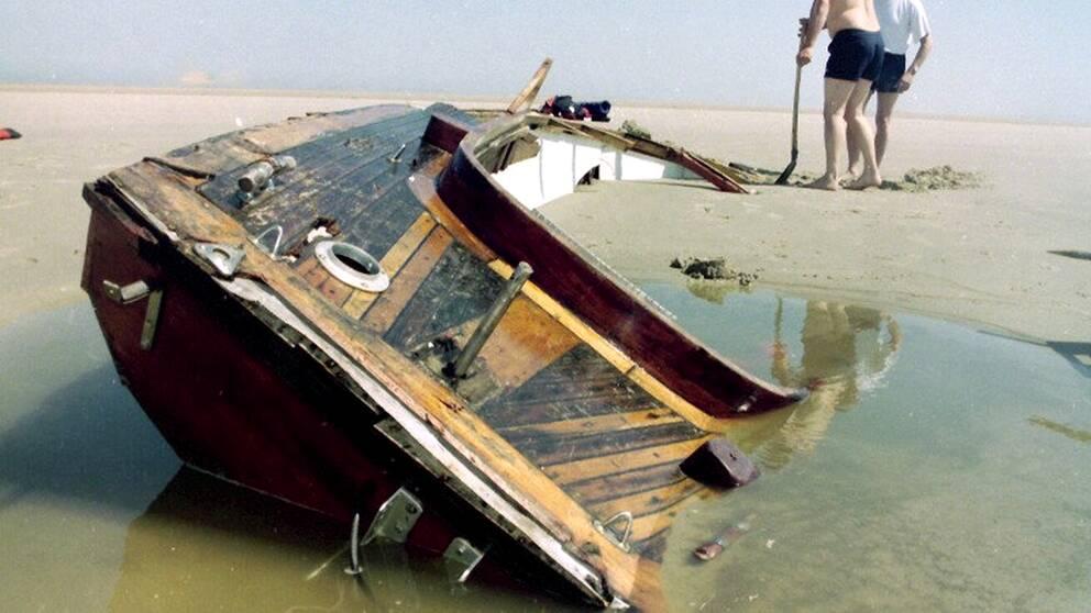 En träbåt till hälften fylld med vatten och sand ligger på en sandstrand.