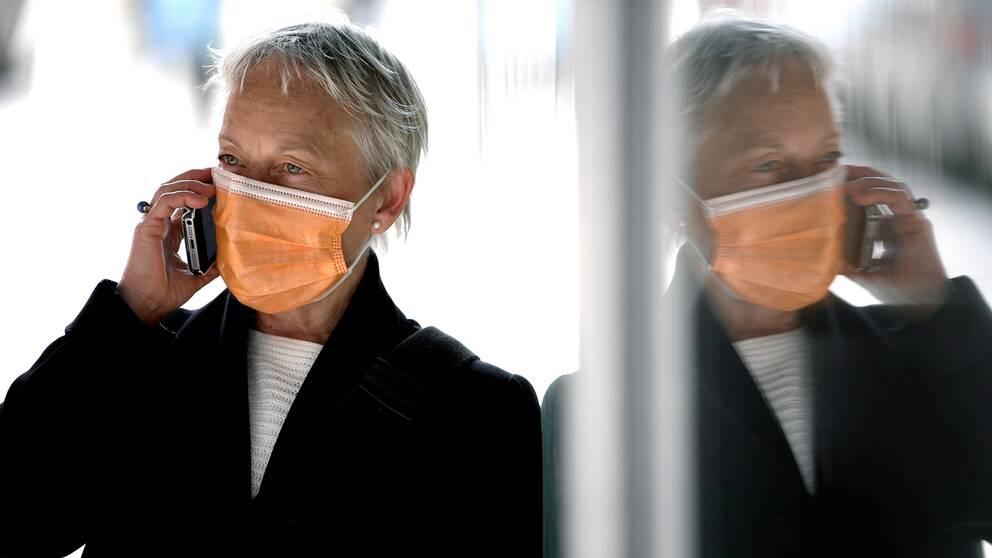En person bär munskydd och prata i mobiltelefon. Bilden är en arrangerad illustrationsbild fotograferad med modell