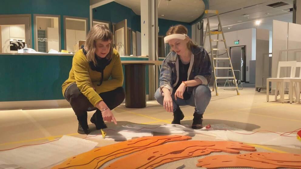 Ann Skagerling och Josefine Åhs Lagerbergs sitter på huk vid ett av konstverken som ska hängas upp i Kronoteket.