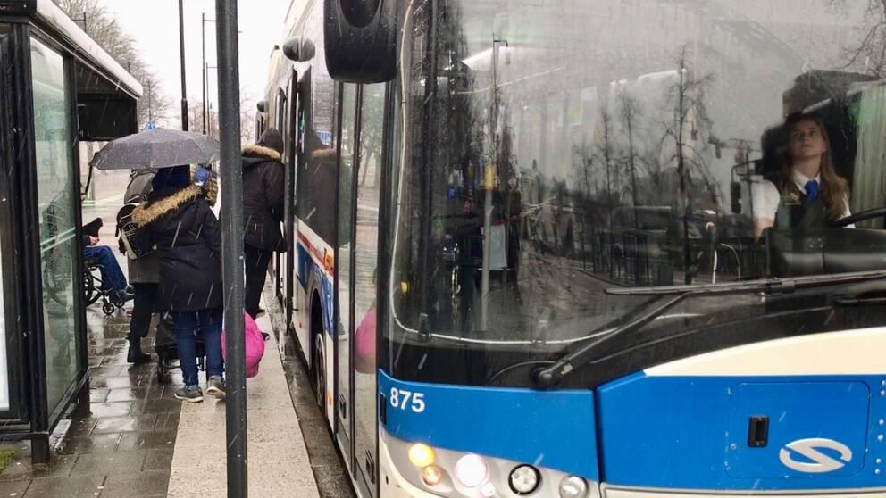 Resenärer går in och ur bussen genom bakdörrarna.