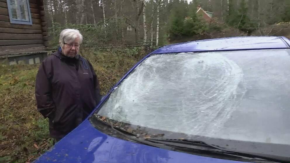 en dam vid en blå bil med krossad ruta