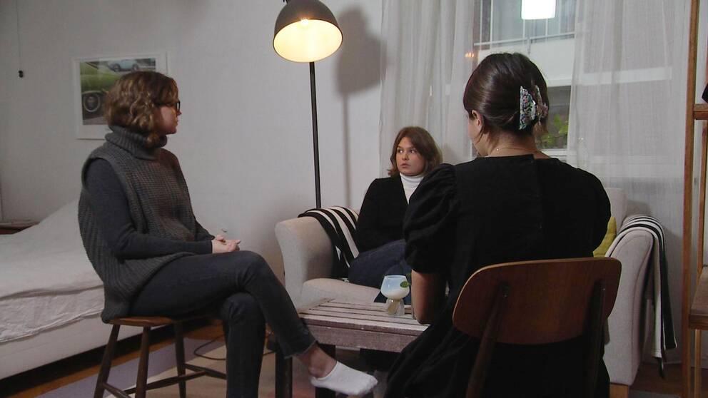 Alicia Hernqvist, Hanna Lindvall och Angele Pesce sitter i ett vardagsrum och pratar.