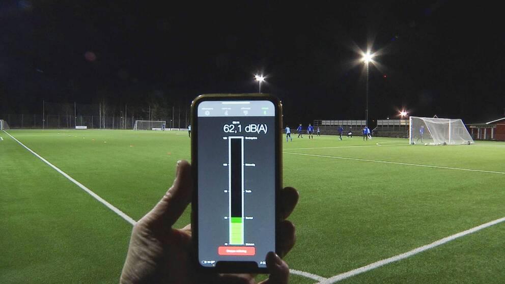 En mobiltelefon där man ser ett mått på ljudnivån hålls upp vid en fotbollsplan där träning pågår.