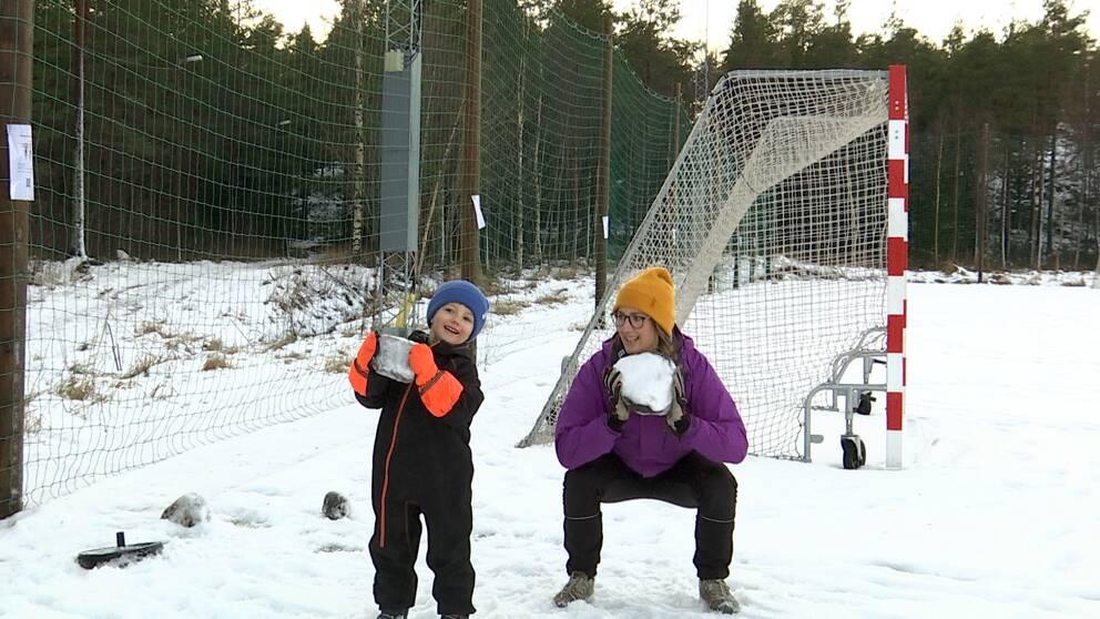 Tjej och hennes son på en snöig fotbollsplan