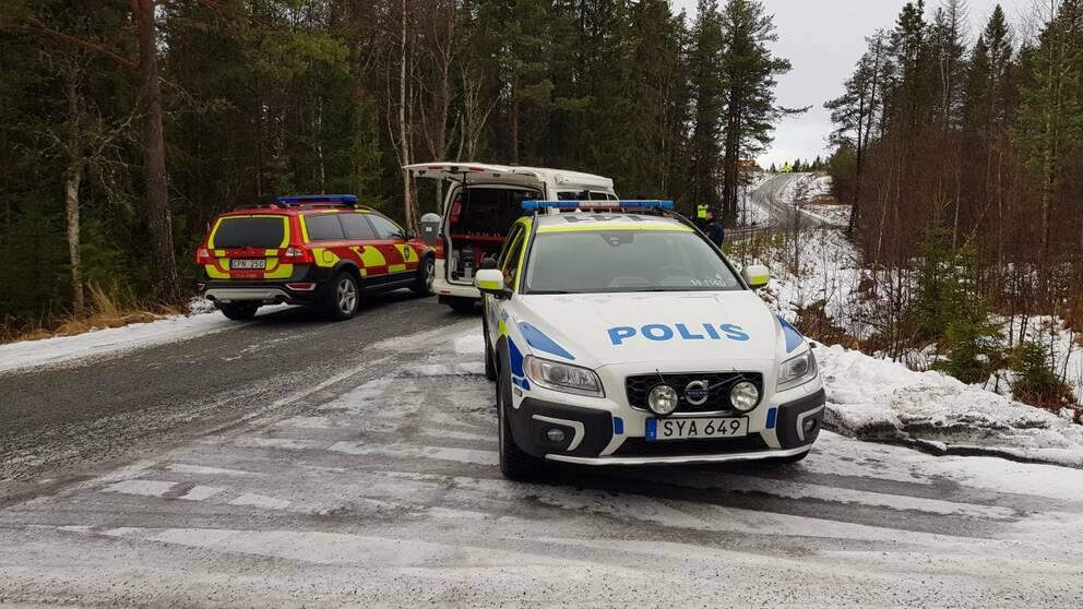 bild på polisbilar och en räddningstjänstbil som blockerar en grusväg.