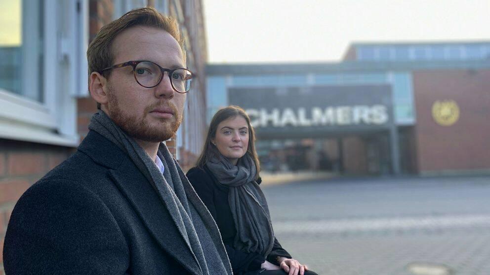 """En man med glasögon och skägg sitter på en bänk och tittar in i kameran. Bredvid sitter en kvinna med mörkt hår. Bakom dem syns en står skylt med """"Chalmers"""" i stora bokstäver."""