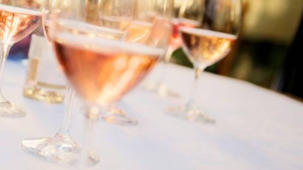 Bilden visar flaskor med rosévin och vinglas på ett bord med vit duk.