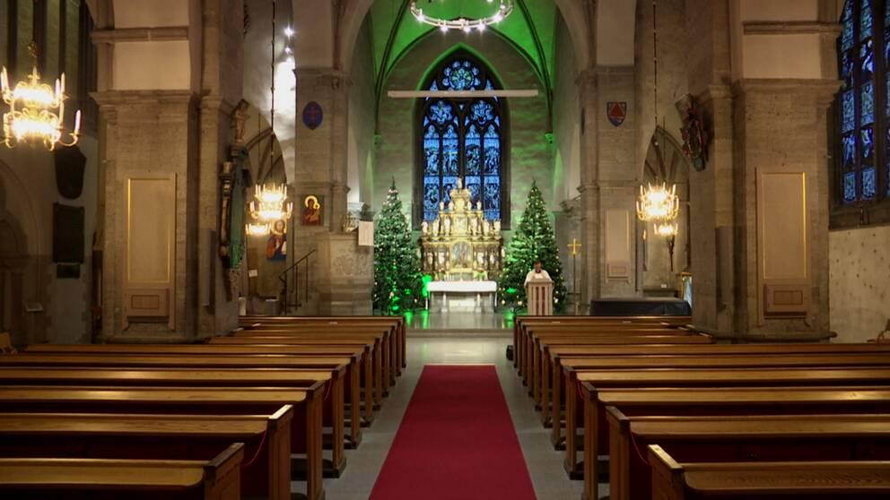 En bild inne i Nikolaikyrkan i Örebro, tomma kyrkbänkar.