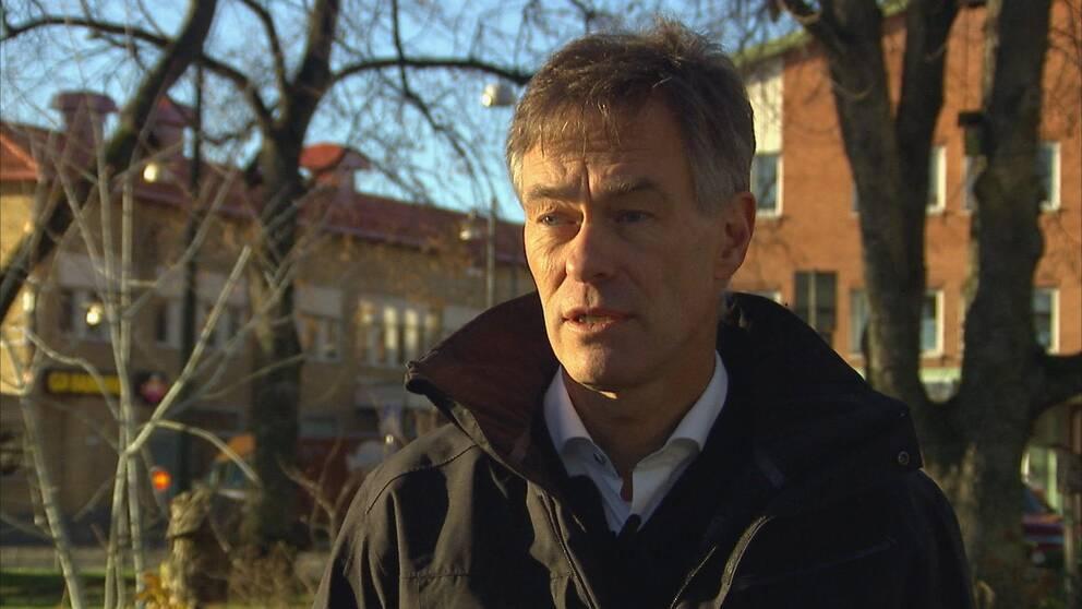 Håkan Axelsson utomhus i Arvika med träd och bostäder i bakgrunden.