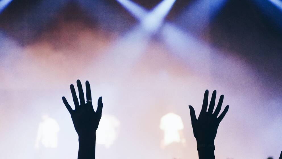 Två händer uppe i luften vid en konsert.