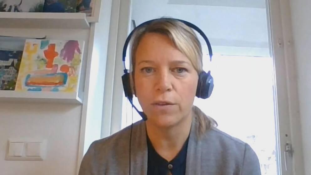 Porträttbild, sitter med headset på, och tittar in i dator.