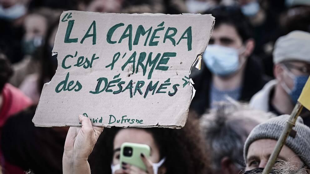 """En demonstrant i Paris håller i en skylt som lyder: """"Kameran är de obeväpnades vapen""""."""