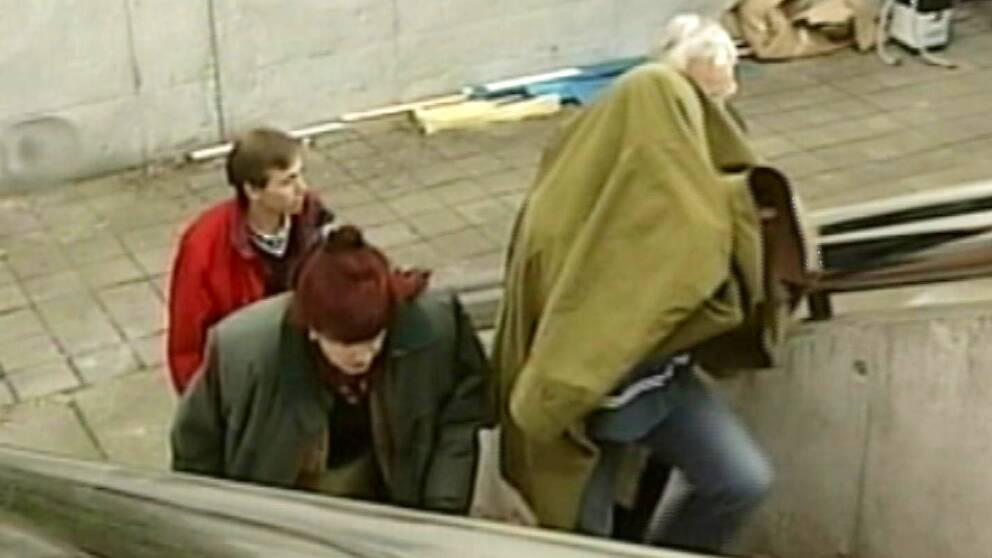 gammal bild av person gömd under en rock som går uppför en trappa, följd av två personer