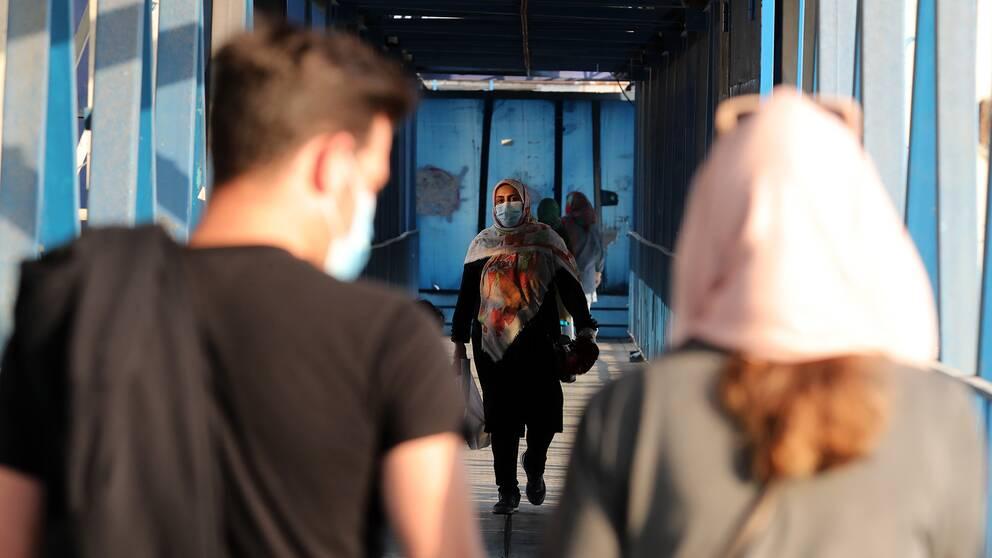 Bild på människor i Teheran under coronapandemin bärandes munskydd.