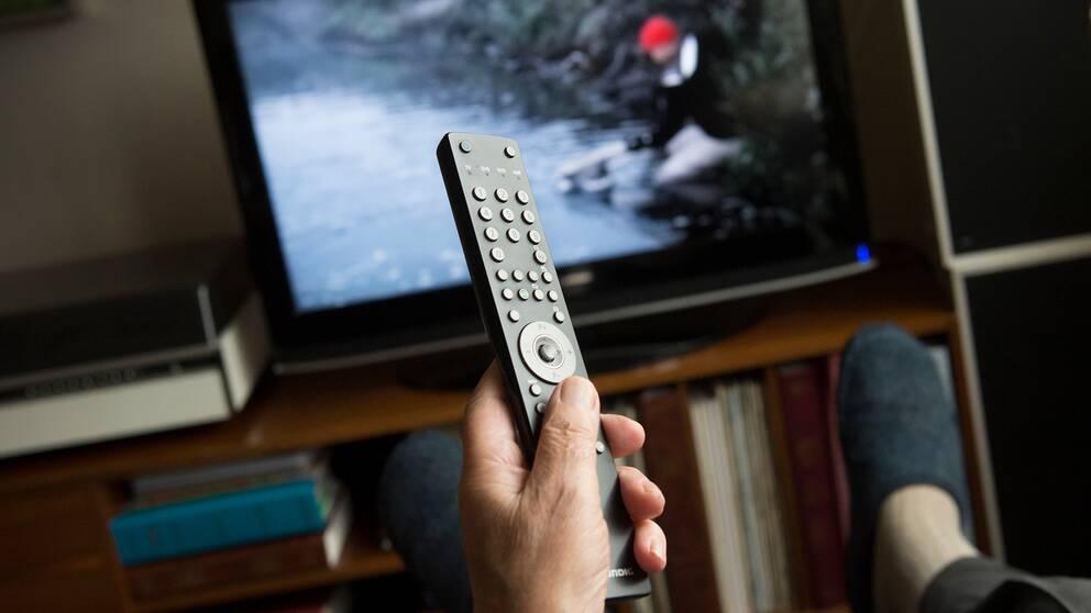 En man håller i en fjärrkontroll framför en tv-skärm.