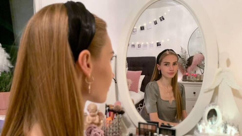 Tjej med långt blont hår och svart hårband tittar in i en spegel. Framför henne står smink och sminkborstar prydligt uppradade.