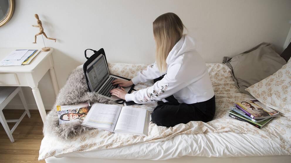 Flicka som sitter med dator på säng.