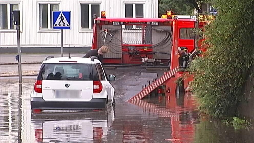 bil bärgas på översvämmad gata