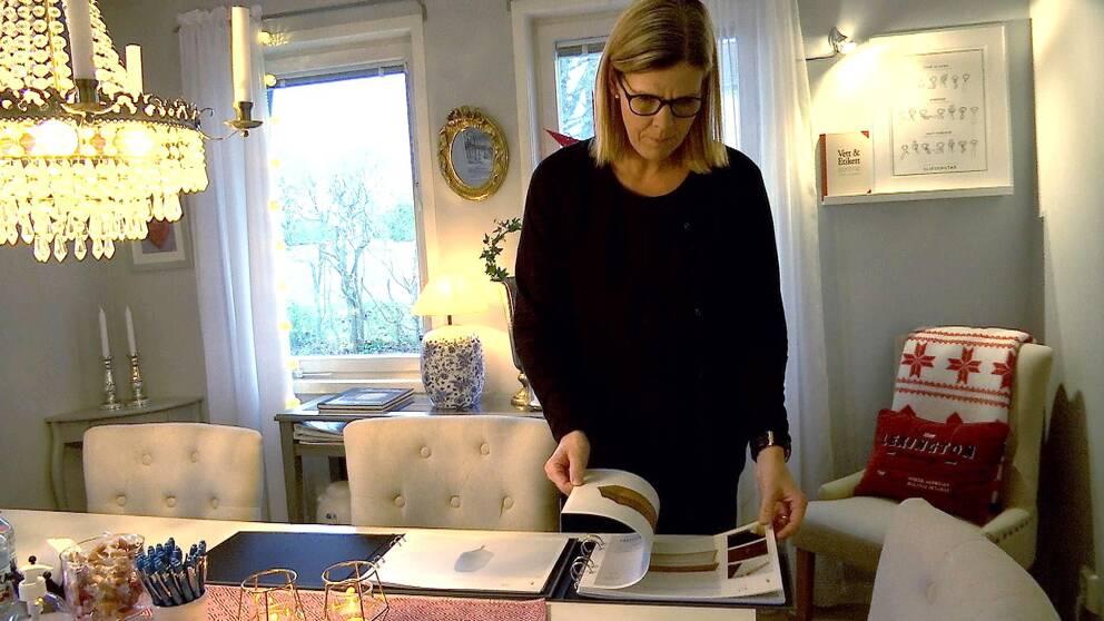 Begravningsentreprenör Annie Wårhem bläddrar i kistbroschyrer