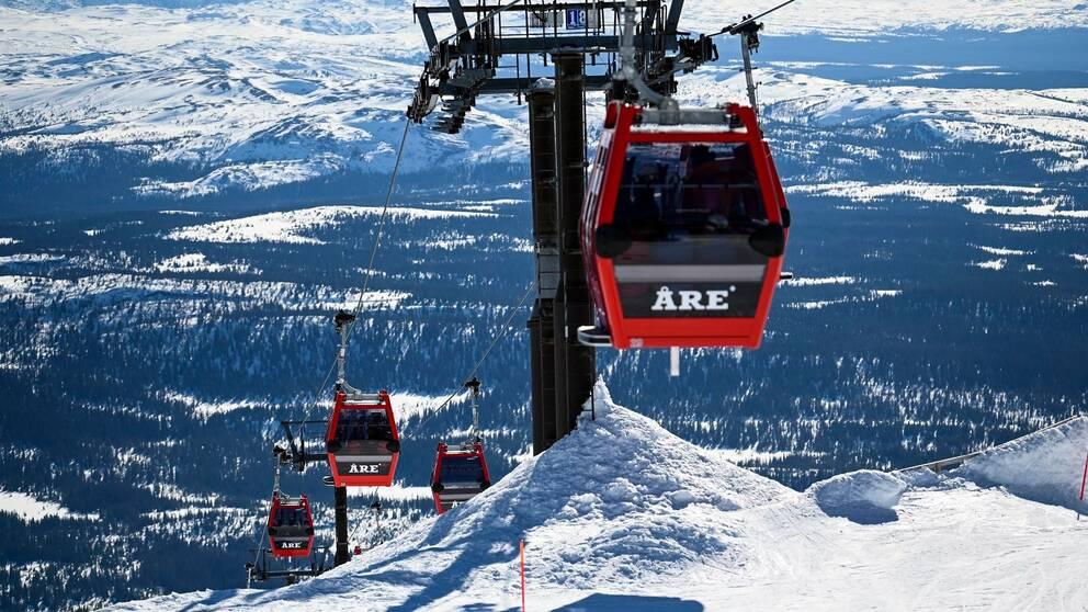 Arkivbild över en skidlift i Åre med röda kabiner med texten Åre. Snö.