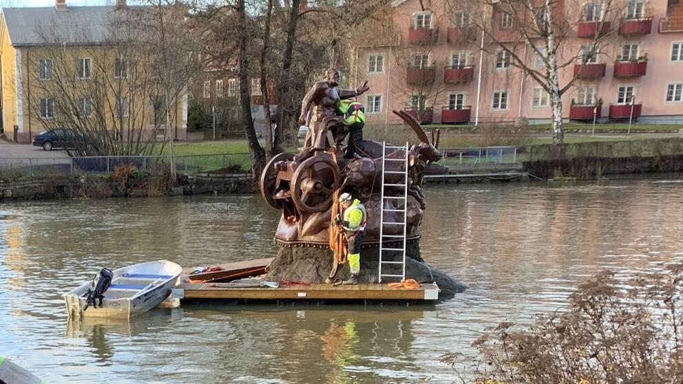 Tors bockar i Torshälla har just lyfts tillbaka i ån. Två flytbryggor och en motorbåt ligger intill statyn. Två personer i varselväst, flytväst och hjälm klättrar med stege på statyn.