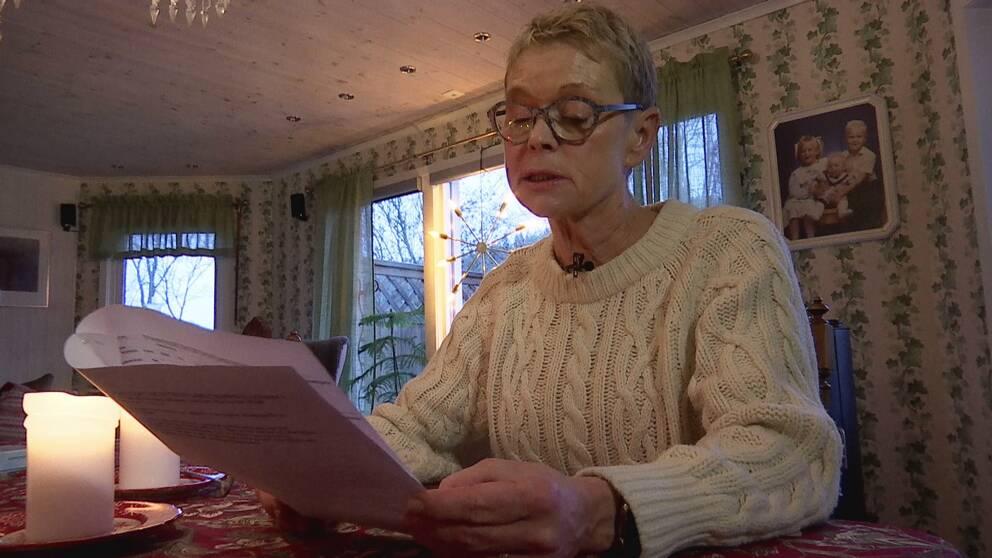 Elisabeth sitter i sitt vardagsrum och läser i ett papper. Hon ser bekymrad ut.