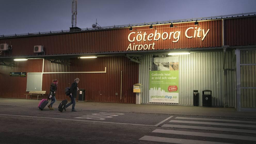 Två personer med resväskor utanför Göteborg City flygplats, som i dag heter Säve flygplats.