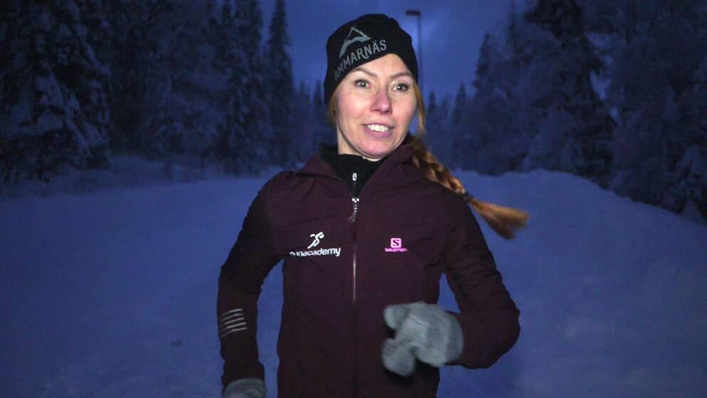 Ung kvinna springer på snöig väg.