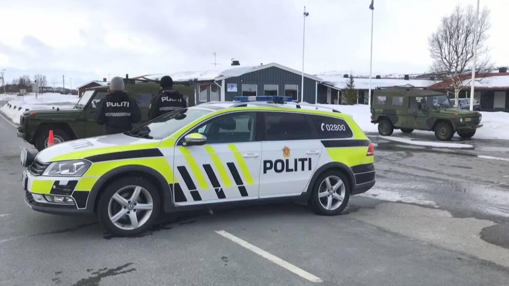 Bild på norsk polisbil på en väg. Två poliser står vid bilen.