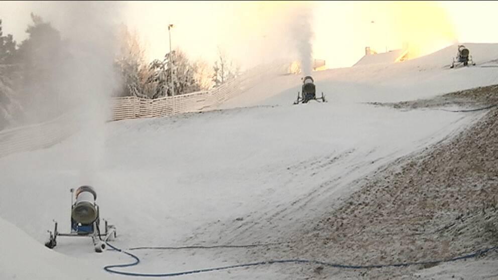 tre snökanoner sprutar ut snö på en delvis bar skidbacke