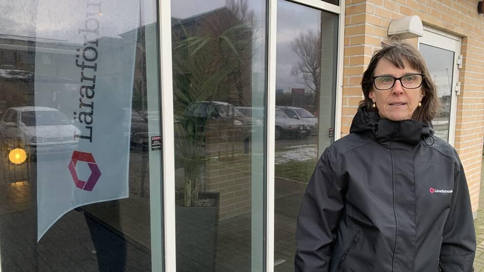 En kvinna står framför en fönsterruta