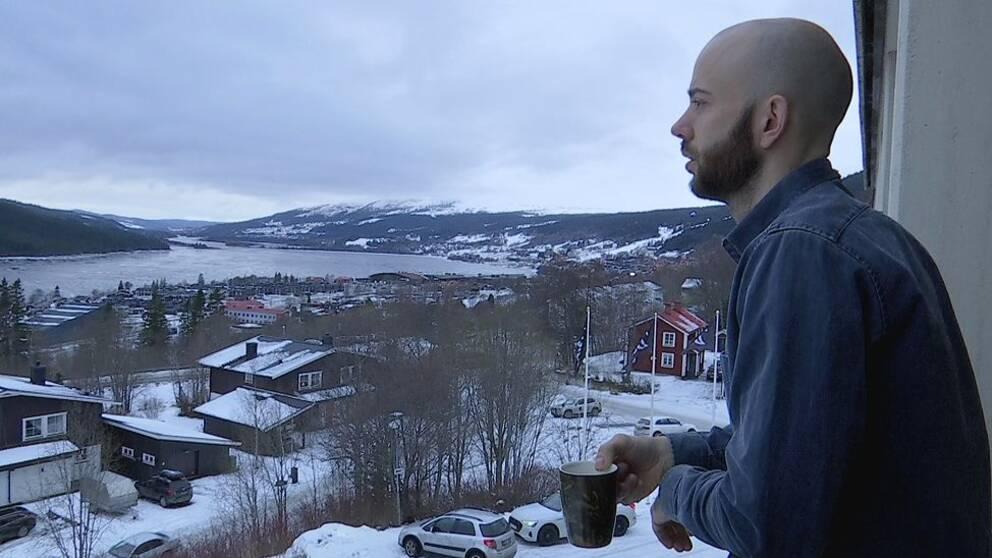 en man på balkong blickar ut över Åre by och Åresjön