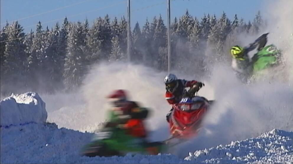 tre snöskotrar i full fart på skotercrossbana