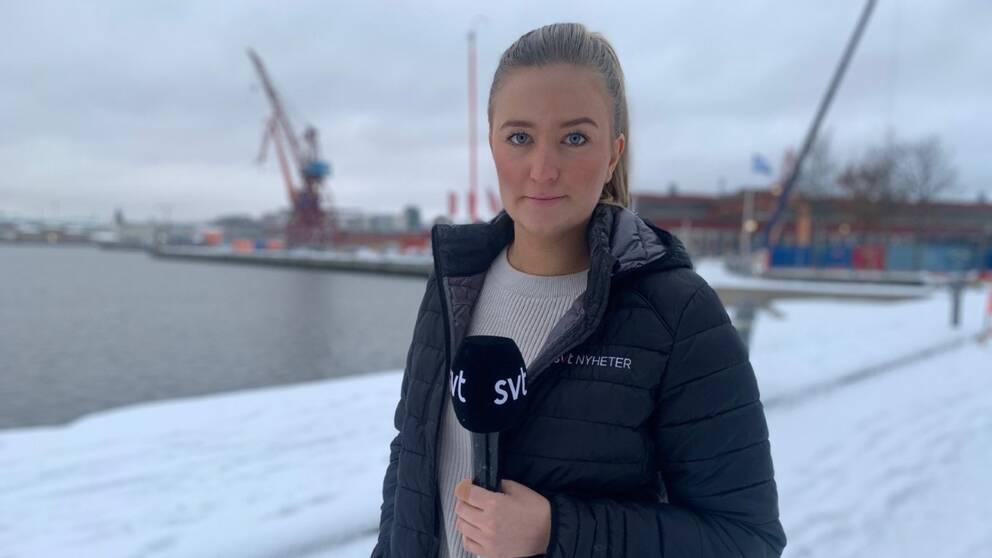 Kvinna med svart jacka med SVT-logga och en mick i handen. I bakgrunden syns Göteborg.