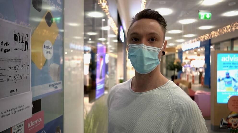 En ung man med munskydd sätter upp en lapp med info om hur många som får röra sig i lokalen samtidigt.