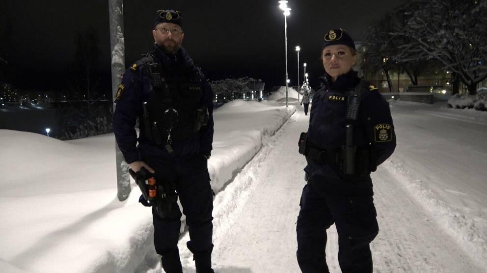 två poliser i unifrom på en snöig gågata upplyst av gatlampor