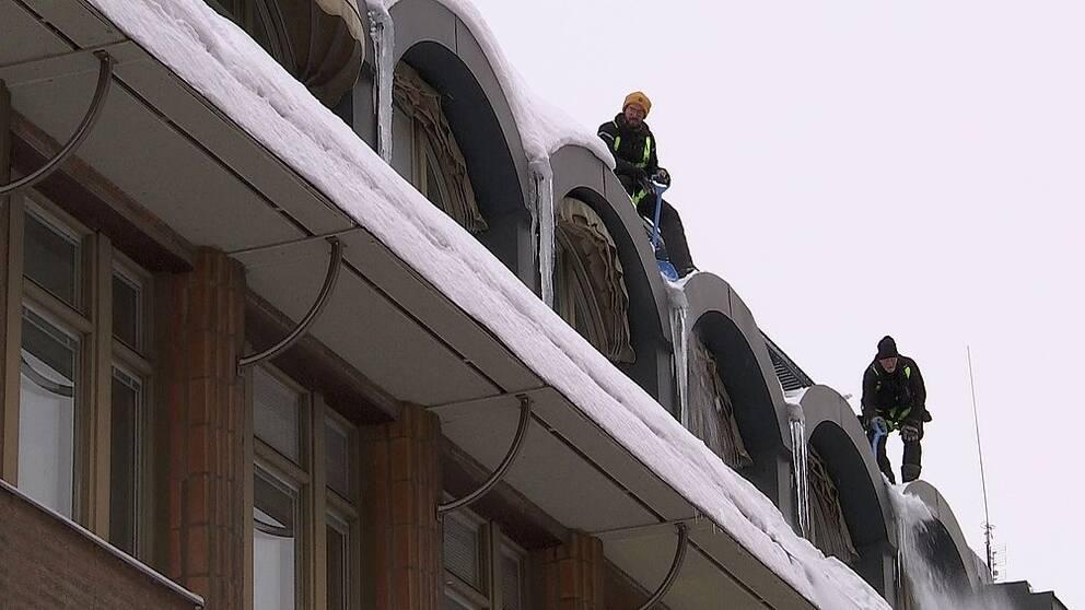 Två snöskottare på ett tak