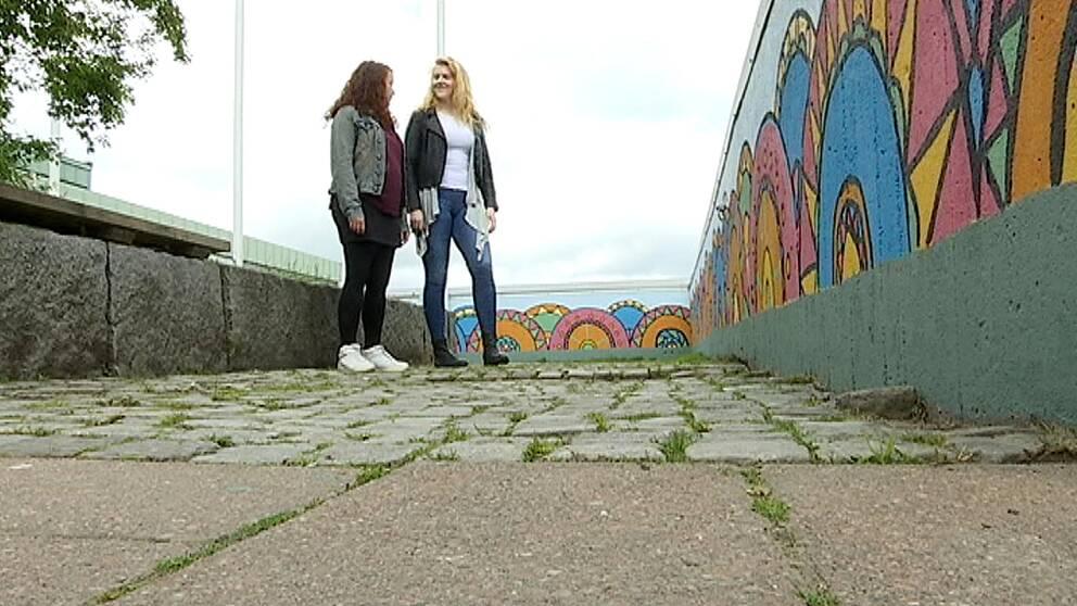 My Wikström och Ingrid Perbo tittar på muralmålningen de gjort på en av Hammarkullens grå väggar.