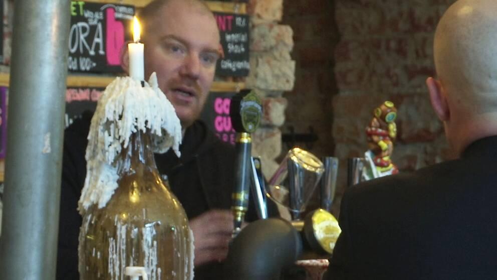 I bilden ser man en krögare som häller upp en öl på fat.