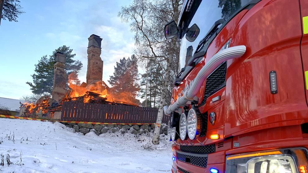 Två murstockar sticker upp från ett nedbrunnet hus. Det brinner fortfarande i bråtet.