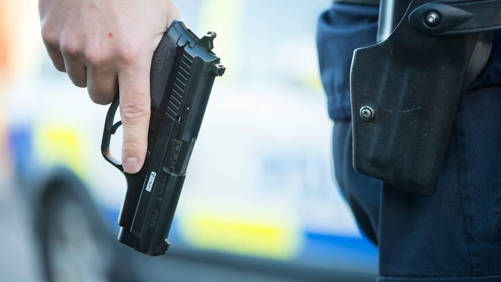 Hand som håller i en pistol, polisens tjänstevapen.