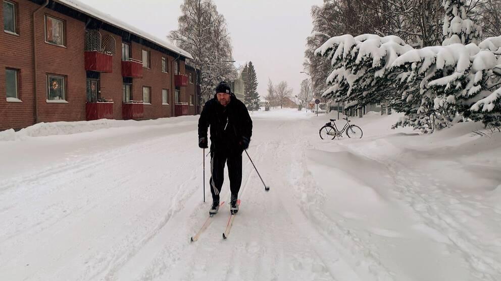 En mörkt klädd man åker skidor på en gata i Östersund