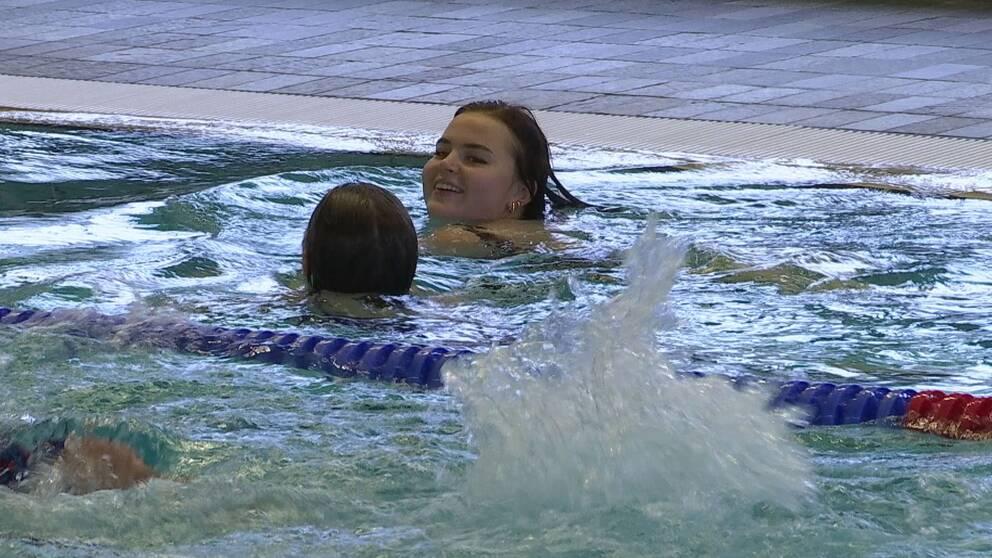 Två barn simmar i en bassäng